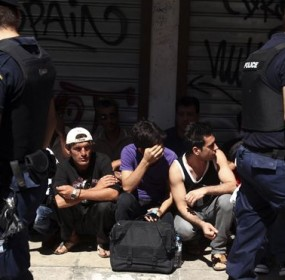 Police detain a group of migrants in central Athens. (AP)